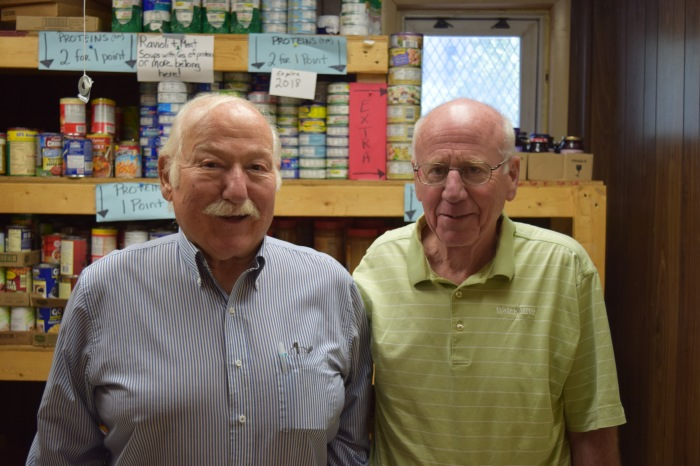 Hank and John, RSVP volunteers, at their volunteer location, our downtown food pantry